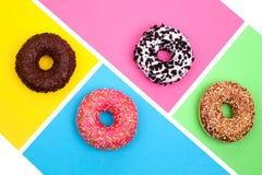 Vier verschillende donuts op heldere multicolored hoogste mening als achtergrond stock afbeeldingen
