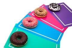 Vier verschillende donuts op heldere multicolored hoogste mening als achtergrond royalty-vrije stock fotografie
