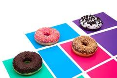 Vier verschillende donuts op multicolored achtergrond royalty-vrije stock fotografie