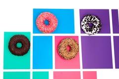 Vier verschillende donuts op multicolored hoogste mening als achtergrond stock afbeelding