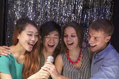 Vier vrienden die samen bij karaoke zingen stock fotografie
