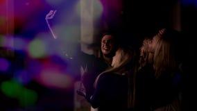 Vier vrienden die selfie op smartphone bij nachtclub, vriendschap en geluk nemen royalty-vrije stock foto