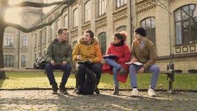 Vier vrienden die toekomstige examens dicussing bij universiteit stock videobeelden