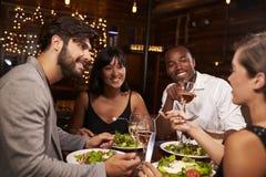 Vier vrienden die van diner en dranken genieten bij een restaurant stock afbeelding
