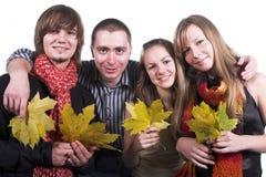 Vier vrienden, meisjes en kerels, met gele esdoorn leav Stock Afbeelding