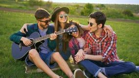 Vier vrienden omhelzen, spelengitaar en zingt in openlucht liederen bij zonsondergang Zeer gelukkig zij en cheerfu stock footage