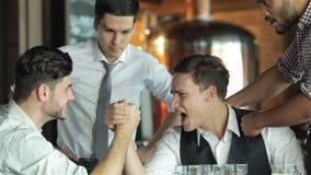 Vier vrienden worstelen op hun handen drinken bier stock videobeelden