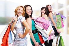 Vier vrolijke volwassen meisjes met aankopen Stock Foto