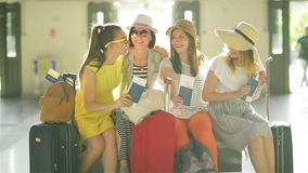 Vier Vrouwelijke Reizigers met Grote Koffers zitten in de Wachtkamer bij de Luchthaven met binnen Paspoorten en Kaartjes stock videobeelden