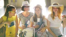 Vier Vrouwelijke Toeristen met Grote Bagage zitten in de Wachtkamer bij de Luchthaven met binnen Paspoorten en Kaartjes stock videobeelden
