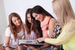 Vier vrouwelijke vrienden die een omslag bekijken Royalty-vrije Stock Foto
