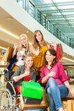 Vier vrouwelijke vrienden die in een wandelgalerij met rolstoel winkelen stock foto's