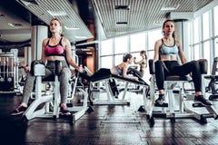 Vier vrouwen die in gymnastiek sterkte opleiding op de simulator doen royalty-vrije stock fotografie