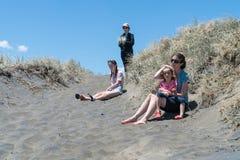 Vier vrouwen in duinen op Muriwai-Strand Stock Afbeelding