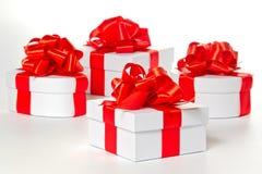 Vier weiße Geschenkkästen mit rotem Satinfarbband Lizenzfreie Stockbilder