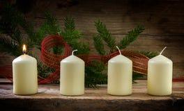 Vier weiße Kerzen, ein Burning auf der ersten Einführung verzierten wi Lizenzfreie Stockfotografie