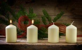 Vier weiße Kerzen, zwei von ihnen brennend auf der zweiten Einführung, De Stockfoto