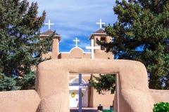 Vier weiße Kreuze und eine Kirche und eine Wand des luftgetrockneten Ziegelsteines Stockfotografie