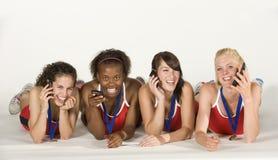 Vier weibliche Athleten, die sich, sprechend an den Telefonen hinlegen Stockfotografie
