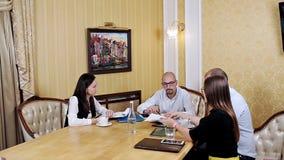 Vier werknemers van prestigieuze internationale firma die over toekomstige overeenkomst bespreken stock video