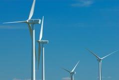 Vier windturbines op blauwe hemel Stock Afbeelding