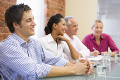 Vier Wirtschaftler beim Sitzungssaallächeln lizenzfreies stockbild