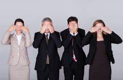 Vier Wirtschaftler, die ihre Augen geschlossen anhalten Stockbilder