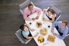 Vier Wirtschaftler, die am Sitzungssaaltisch essen Lizenzfreie Stockbilder