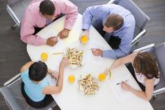 Vier Wirtschaftler, die am Sitzungssaaltisch essen stockfotografie