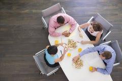 Vier Wirtschaftler, die am Sitzungssaaltisch essen stockfotos