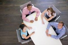 Vier Wirtschaftler am Sitzungssaal legen das Lächeln ver Lizenzfreie Stockfotos