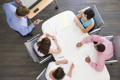 Vier Wirtschaftler am Sitzungssaaltisch lizenzfreie stockfotos