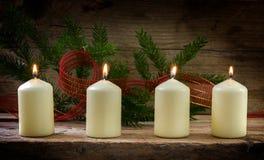 Vier witte brandende kaarsen op de vierde komst, worden verfraaid die met Royalty-vrije Stock Afbeelding