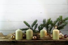 Vier witte kaarsen, één van hen die op eerste komstchri branden stock foto's