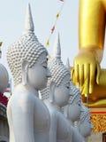 Vier witte standbeelden van Boedha met het gouden standbeeld van Boedha op de achtergrond Stock Foto