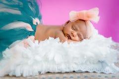 Vier-Wochen-Babysäuglingsmädchen-Studiofoto, das auf tragendem Ballettröckchen und Bogen des flaumigen Kissens schläft Stockbilder