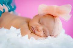 Vier-Wochen-Babysäuglingsmädchen-Studiofoto, das auf tragendem Ballettröckchen und Bogen des flaumigen Kissens schläft Stockfoto