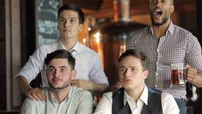 Vier zakenliedenventilators die bier drinken en verheugen zich stock video