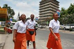 Vier zwarte Afrikaanse vrouwen in eenvormige, oranje rokken en witte shi Stock Afbeelding