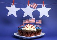 De Amerikaanse vlaggen van de V.S. met sterren die van pinnen op een lijn hangen en cupcakes met exemplaarruimte. Stock Fotografie