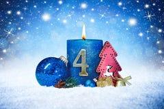 Vierde zondag van komst blauwe kaars met de gouden rode decoratie van het metaalaantal op houten planken in sneeuwvoorzijde van z stock foto's