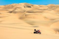 Viererkabel, das in Sandwüste fährt ATV in der Mitte von nirgendwo stockbilder
