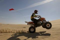 Viererkabel-Fahrrad Rider Doing Wheelie In Desert Stockbilder