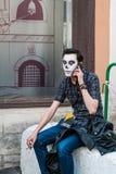 Viering van de Dag van de Doden Een mens als skelet wordt vermomd zit, rookt en spreekt op de mobiele telefoon die Stock Foto