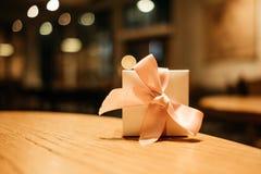 Vierings achtergrondgiftvakje plaats op houten lijst in restauran stock foto's