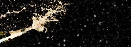 Vieringsthema met het bespatten van champagne op zwarte achtergrond met sneeuw en beschikbare ruimte Kerstmis of Nieuwjaar, Valen royalty-vrije stock afbeelding