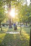 Vierjähriger blonder Junge in einer grünen Jacke lächelt und sitzt in a Lizenzfreie Stockfotos