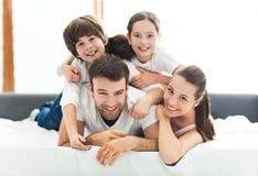 Vierköpfige Familie, die auf Bett liegt Lizenzfreies Stockfoto