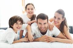 Vierköpfige Familie, die auf Bett liegt Lizenzfreies Stockbild
