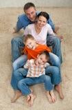Vierköpfige Familie, die auf dem Teppich sitzt Stockfoto